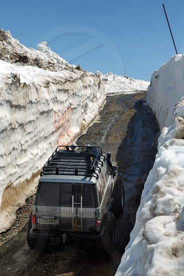 KAMCHATKA PENINSULA RUSSIAN FAR EAST - JUNE 18 2017: Japanese off-road cars Toyota Land Cruiser Prado driving on mountain road in snow tunnel surrounded by high snowdrifts on Vilyuchinsky Pass. photo