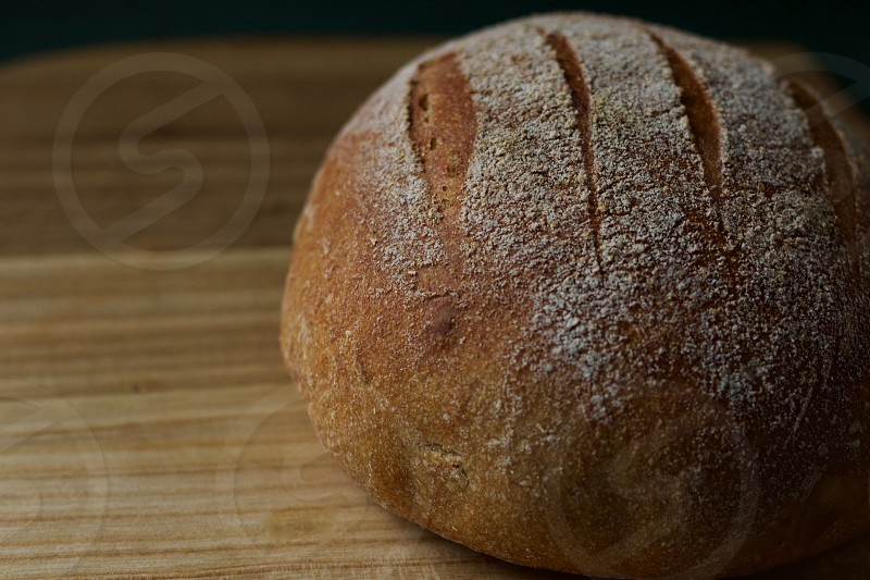 A freshly baked round loaf of sourdough bread on a wooden surface photo