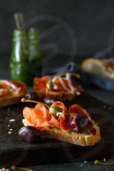Parma ham and olives bruschetta on a dark rustic background photo