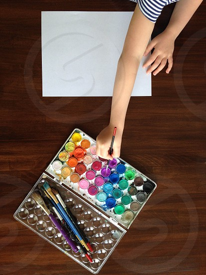 Young hands reaching out to pick their color; painting with watercolors photo