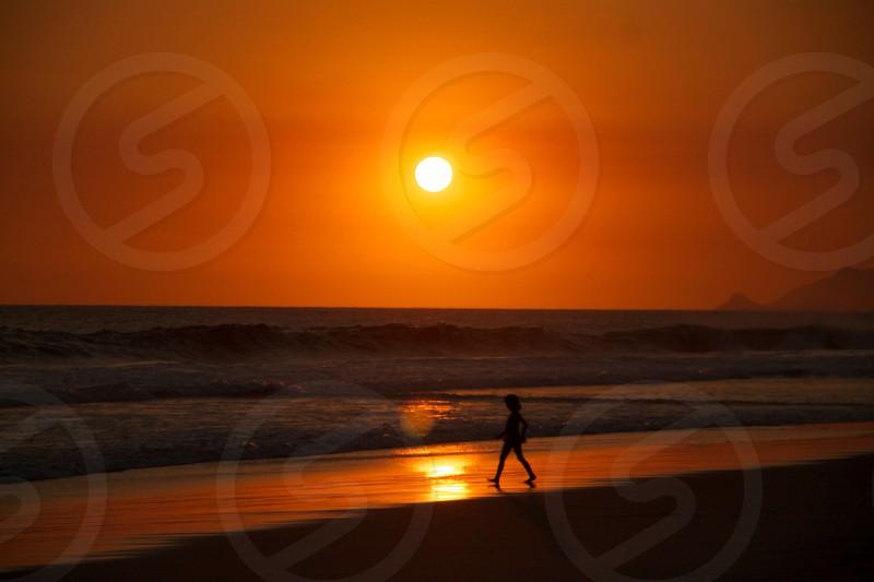 girl walking on seashore on sunset photo