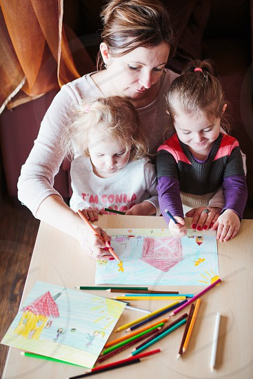 Mom with little girls drawing a colorful pictures of house and playing children using pencil crayons sitting at table indoors. Shot from above photo