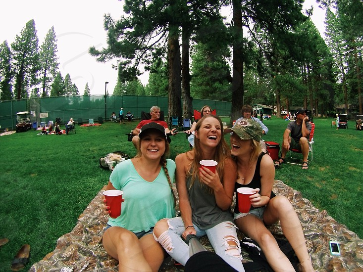 three women sitting on mat while holding red cups and taking picture photo