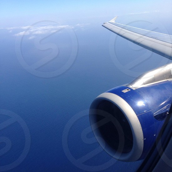 blue and gray airplane engine and wing over ocean photo
