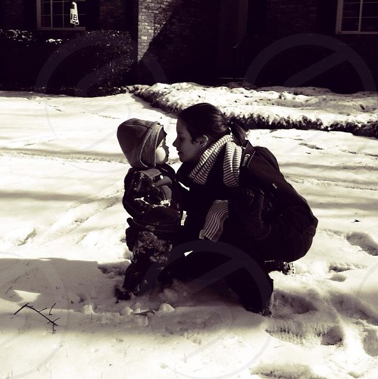 woman kneeling in snow next to small boy photo