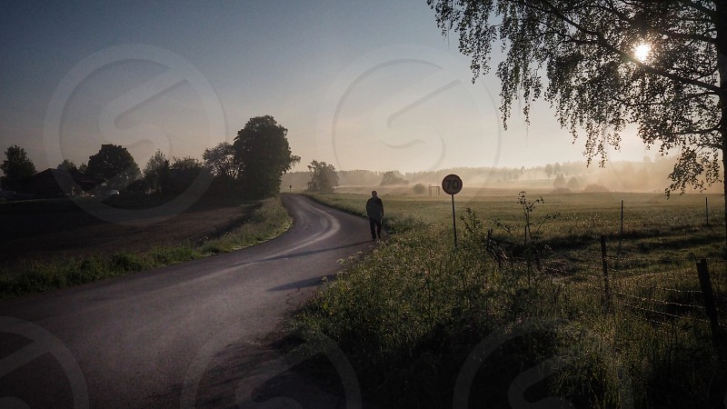 Walking man road scenic road countryside country roads silhouette road sign sunrise morning early morning Sweden  photo