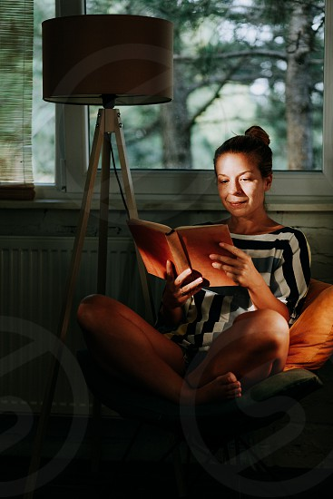 Young woman reading a book at home by the window photo
