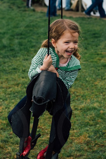 a young girl on a horse swing or tire swing smiling and laughing with a green striped shirt and green grass. photo