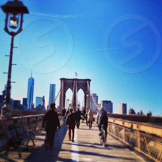 people walking across brooklyn bridge photo