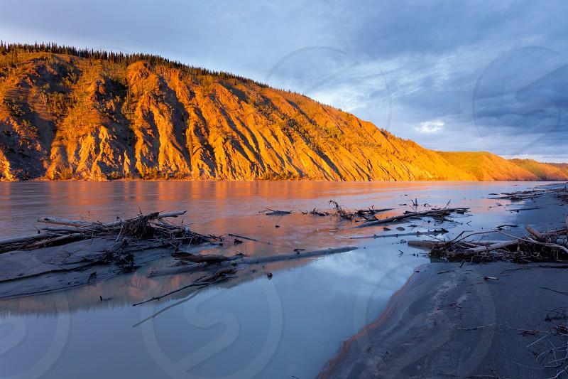Eroded clay cliff river bank at Yukon River Yukon Territory Canada near Dawson City glowing in orange light of summer sunset sun photo