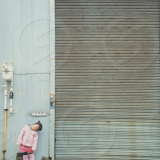 girl in pink skirt and coat in front of metal industrial door photo