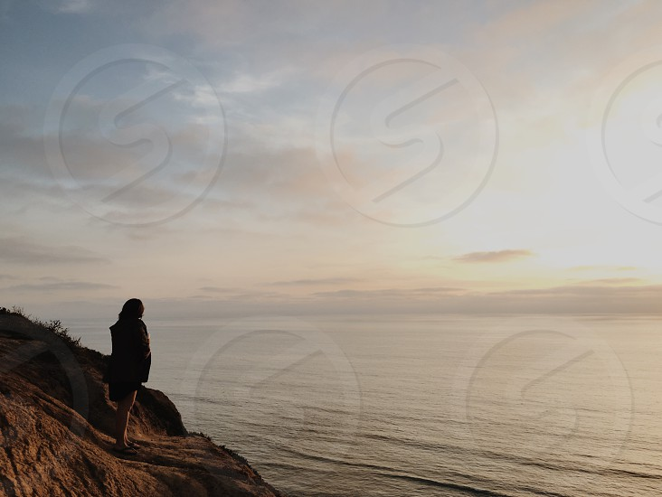 woman standing on a cliff edge overlooking open waters at sunset photo