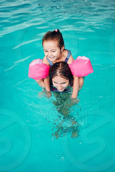 Young woman teaching to swim her younger sister and playing with her in swimming pool. Candid people real moments authentic situations photo
