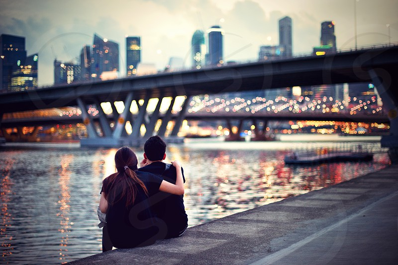 couple sitting on concrete by lake photo