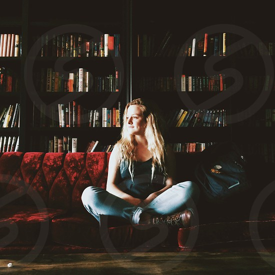 woman sitting on sofa by book case photo