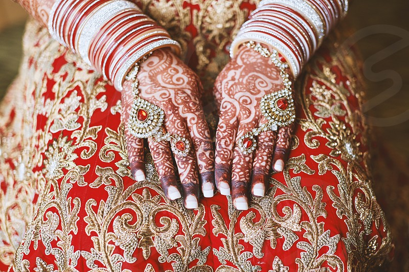 The close-up shot of Indian bride with beautiful red saree showing mehndi (henna) tattoo hand with a lot of glitter bracelets (bangles) on her wrist and wedding rings photo