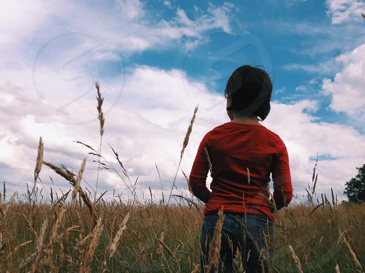 child standing in field photo