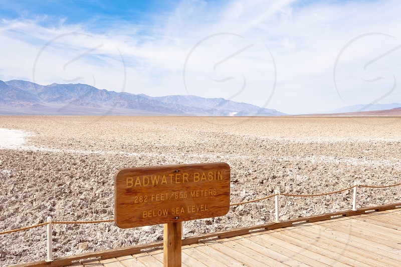 Public Boardwalk with signpost in Badwater Basin lowest point below sea level of Death Valley desolate desert landscape Death Valley National Park California CA USA photo