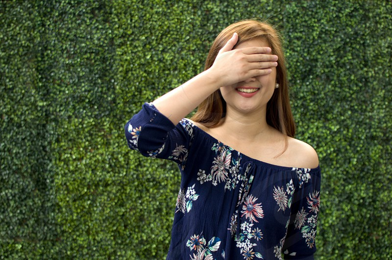 A portrait of a woman wearing a blue floral dress is covering her face with hand photo