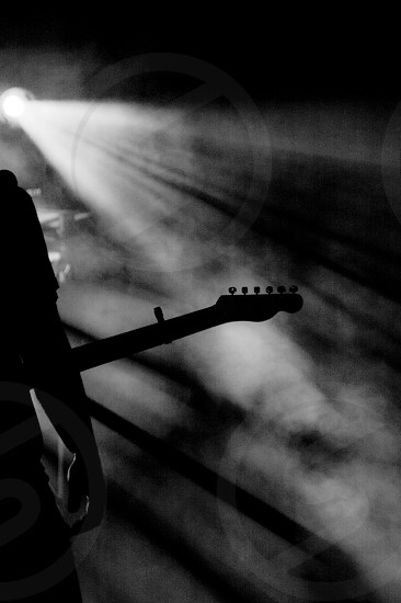shape of guitarist on foggy stage photo