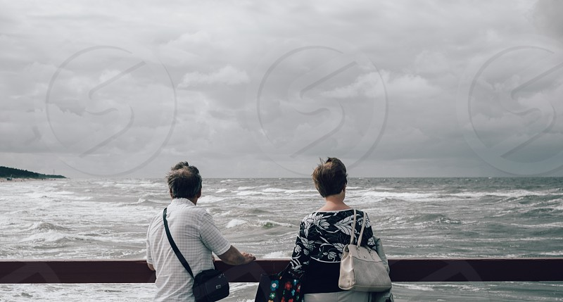 woman and man looking at the sea photo