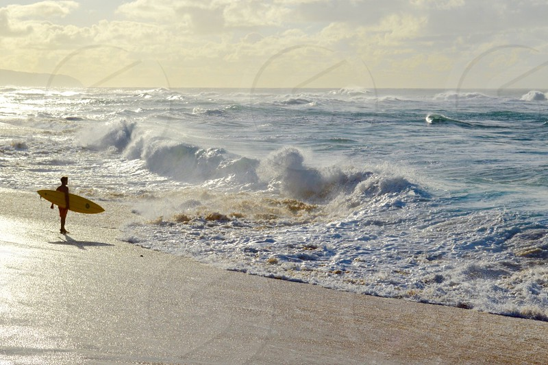 man in orange board shorts holding yellow surfboard on seashore during day time photo