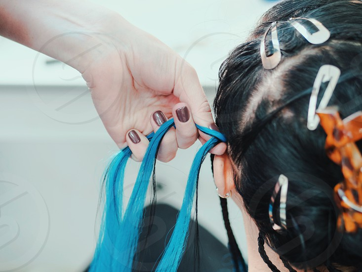 Process of weaving African braid with kanekalon. Small afrobraids with blue strands. Topical hairstyle - bright braids. Master plaits with artificial material photo