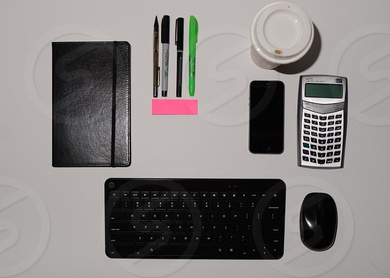 Notebook keyboard cell phone coffee cup pens highlighters mechanical pencil calculator sticky notes photo