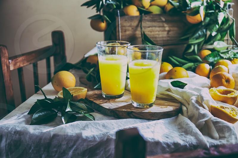 ORANGE. Haervest concept. Orange juice full box of orange fruits ant orange tree branches on table with linen tablecloth. photo