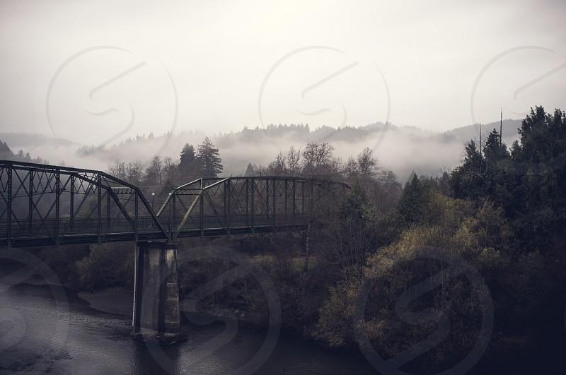 Iron truss bridge over river. Foggy hills. California coast. photo