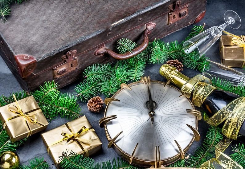 NEW YEAR TRADITION walking with empty suitcase at midnigth for have travel. Funny ritual for New Years Eve. Flat lay composition witn vintage siutcase clock and holiday decoration. photo