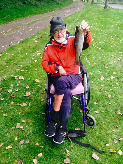 Man in wheelchair holding up a trout he has caught photo