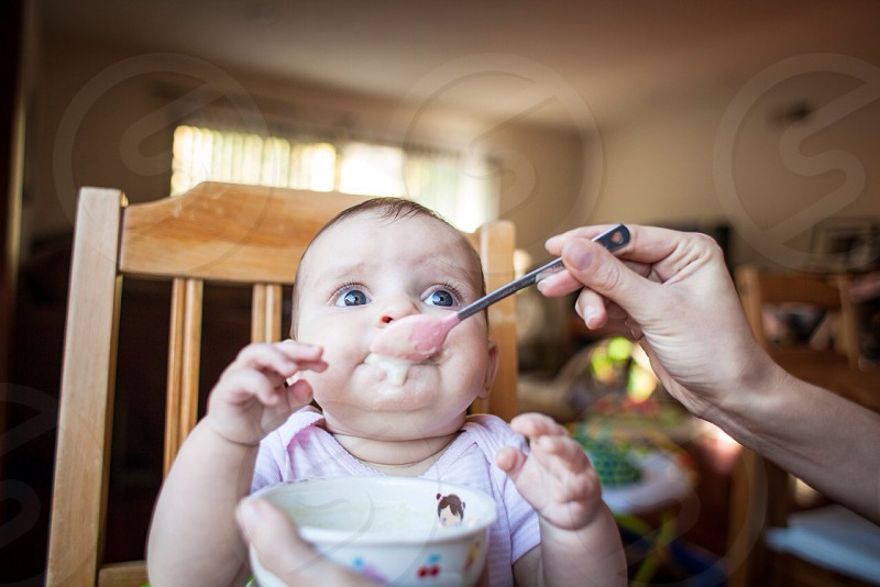 baby with stainless steel dining spoon on mouth photo