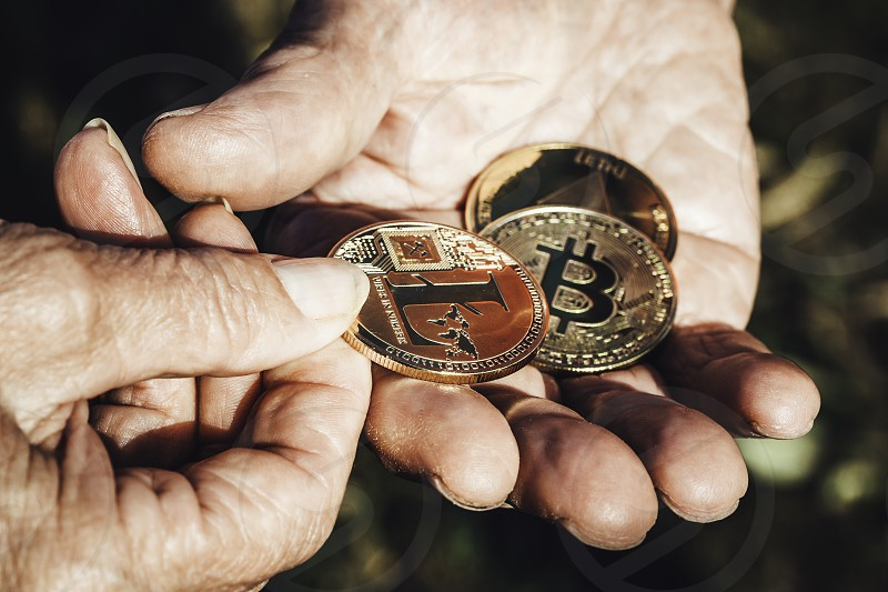 Senior woman hand is holding cryptocurrency coin in focus giving to senior man hand. Business Finance Investment and exchanging concepts photo