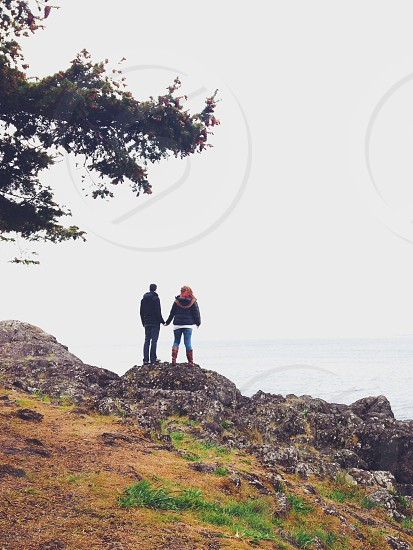 woman wearing black jacket holding hands of man wearing black jacket white standing on rock photo