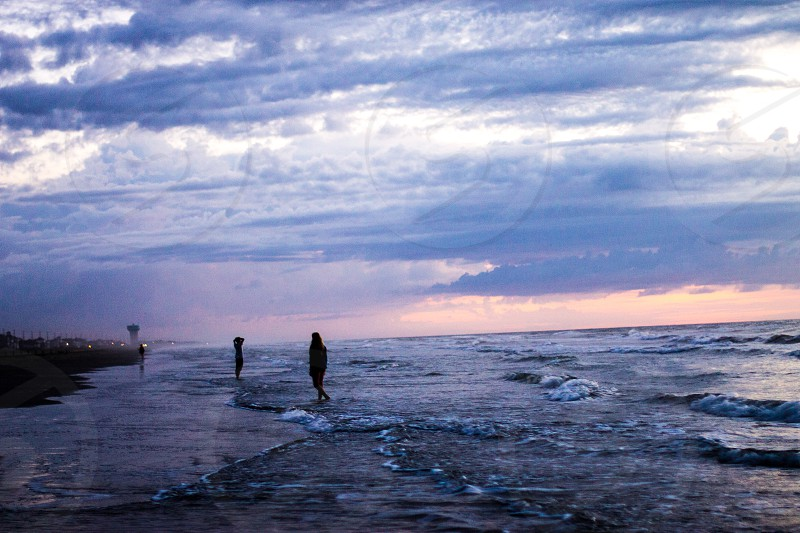 2 persons standing on the seashore photo