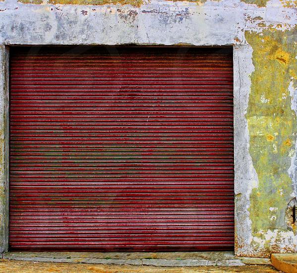 Old red metal accordion style garage door. photo