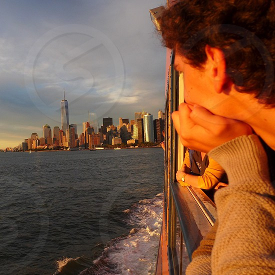 man looking at the sea overlooking the city photo