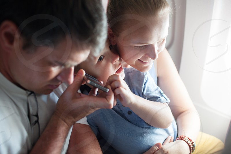 Mother father and little son in the airplane. The have handsfree talking on the cell or listening something photo