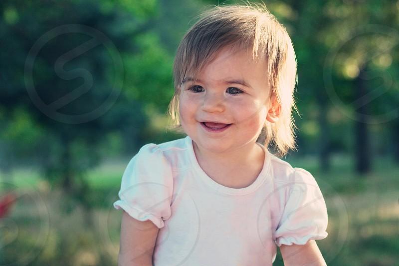 girl in white ruffled dress smiling photo