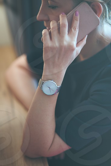 Elegant woman talking on mobile phone wearing silver wristwatch with bracelet and blue dress photo