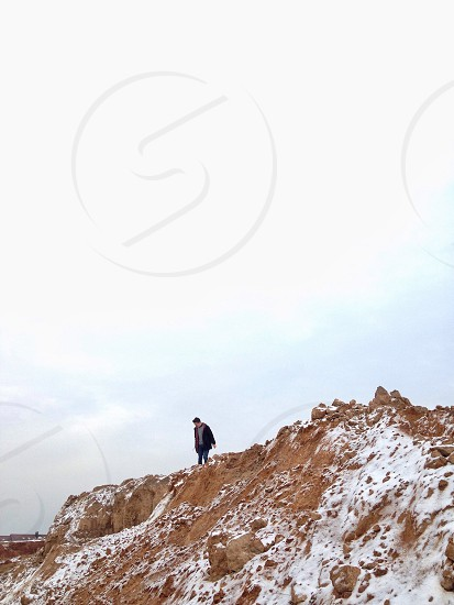 person in black jacket standing on top of hill photo