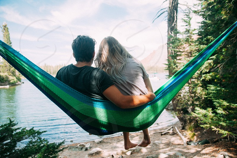 man and woman sitting in green and blue sling hammock near lake photo