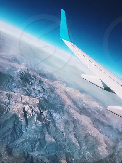 Mountains seen through the window of an airplane. Wing of the airplane landing at the airport seen through the window. Andes mountain in the background.  photo