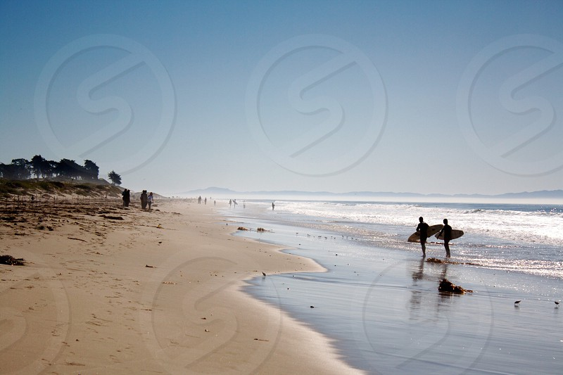 two people standing near seashore during daytime photo