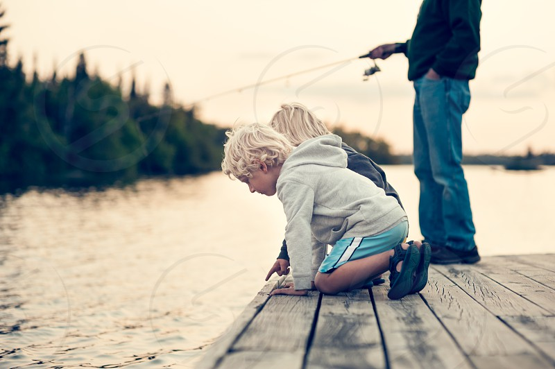 child children fishing boys family people youth kids grandpa generations wonder looking sweatshirt lake water dock blue navy gray yellow trees fish pole rod blonde hair sandals reel sunset dusk evening forest woods vacation relax peaceful serenity wilderness outdoors outside photo