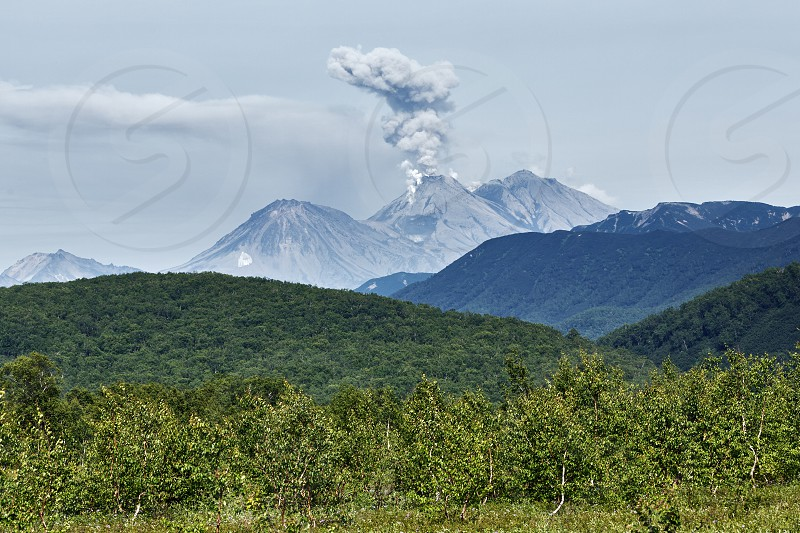 Beautiful summer volcanic landscape of Kamchatka Peninsula: view of explosive-effusive eruption of Zhupanovsky Volcano powerful plume of gas steam ash from crater active volcano. Russian Far East. photo