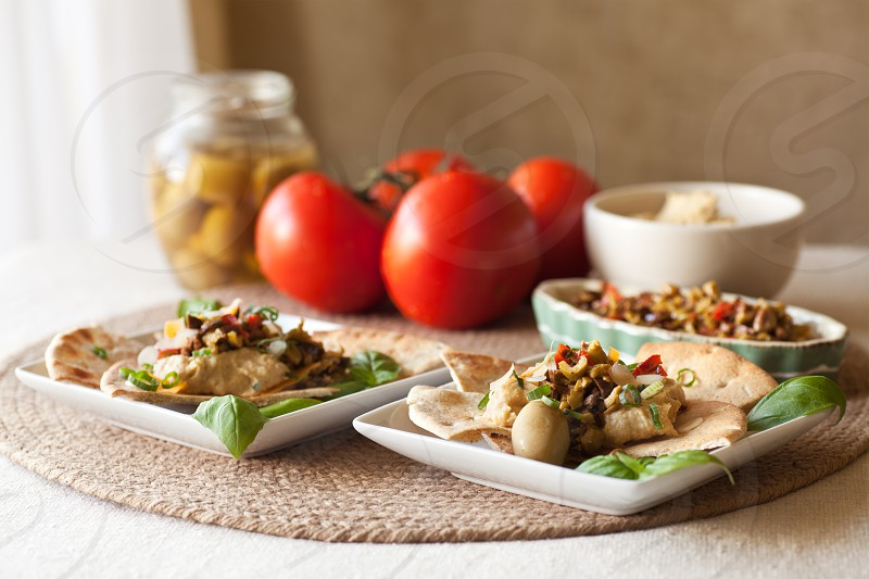 Served on toasted pita wedges: hummus dip and olive bruschetta.  photo