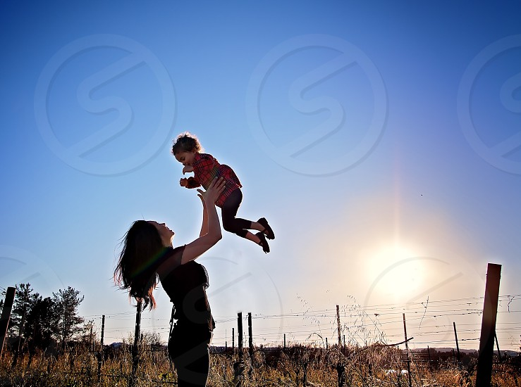 woman with long wavy hair tossing a toddler in the air in a fenced field under a sunny blue sky photo
