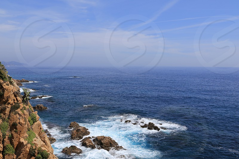 Top view on the rock in the deep blue sea on a sunny summer day photo
